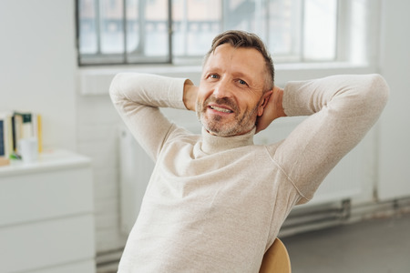 Happy successful businessman relaxing in the office leaning back in his chair with his hands behind his neck smiling at the camera Banque d'images