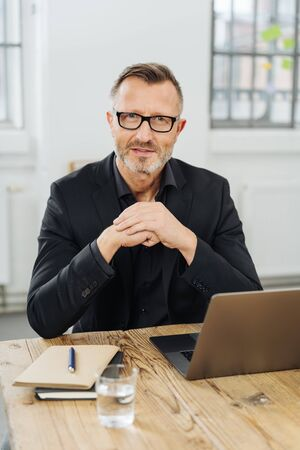 Perplexed businessman staring at the camera with an intense speculative expression as he sits at his desk Stock Photo