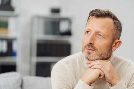 Middle-aged man sitting daydreaming with a serious thoughtful expression and his chin resting on his hands at home on the sofa