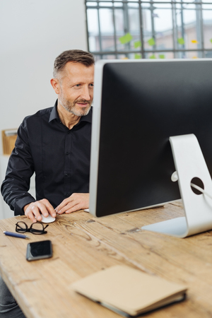 Businessman working at a large desktop computer monitor concentrating on the screen viewed around the side Stock Photo