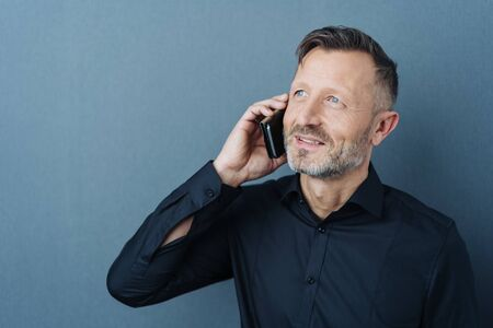 Studio shot portrait of a middle-aged man smiling while talking on mobile phone against gray background for copy space Banque d'images