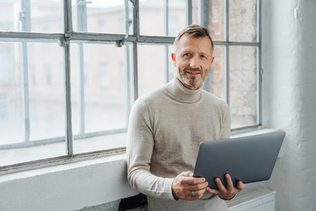 Man holding an open laptop looking thoughtfully at the camera as he relaxes leaning against a large bright window with copy space Banque d'images