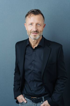 Studio shot portrait of a handsome middle-aged man smiling while wearing elegant black shirt and jacket against gray background for copy space