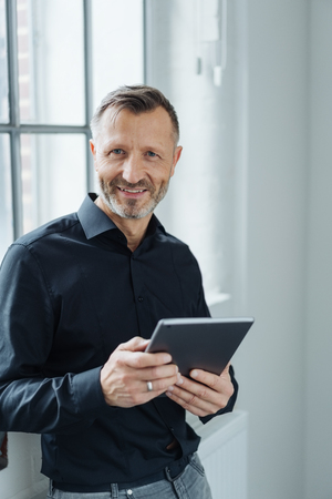 Portrait of a happy and confident middle-aged man looking at camera while holding a tablet PC in the office