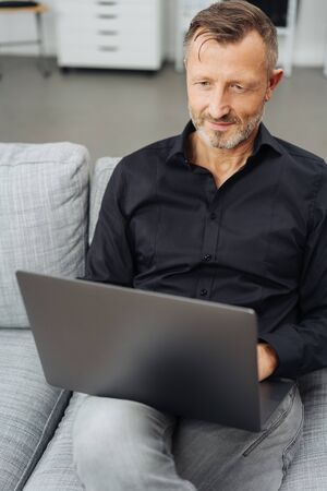 Man using a laptop on a sofa at home balancing it on his lap as he reads data on the screen in a close up view