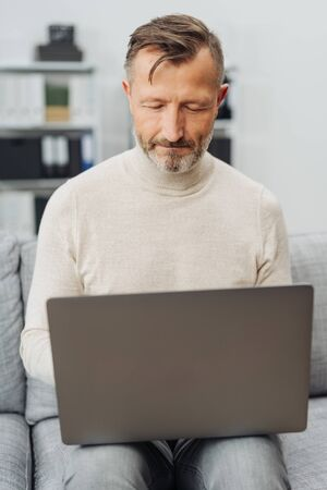 Middle-aged man sitting at home on a sofa using a laptop typing information with a look of concentration