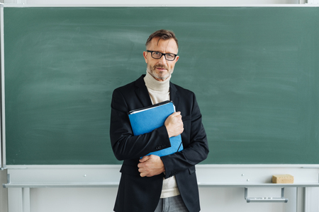 Portrait of a dedicated middle-aged teacher holding a blue folder while looking at camera in the classroom of a modern school or university Banque d'images