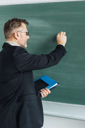 Male teacher writing on a blank chalkboard while holding class notes in his hand in a close up side view