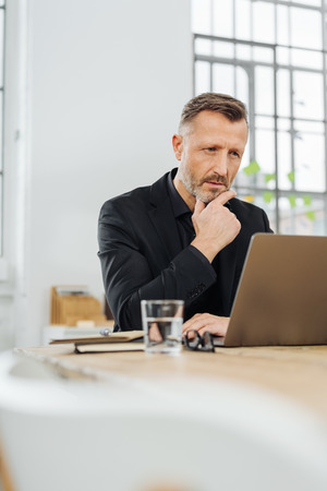 Businessman engrossed in his work at the office sitting reading a laptop with his hand to his chin