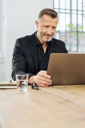 Businessman sitting peering at his laptop screen with an intent expression as he works at a table in a bright office, low angle view with copy space