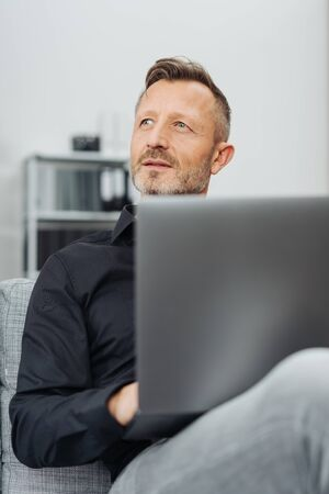 Thoughtful middle-aged man sitting gazing upwards on a comfortable sofa with a laptop balanced on his lap