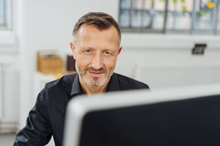 Businessman glancing over the top of his monitor at the camera with a thoughtful expression