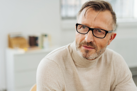 Bearded middle-aged man wearing glasses sitting in an office staring to the side with an attentive expression as though waiting for a response or pondering a problem Banque d'images