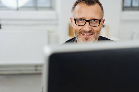 Businessman wearing glasses smiling over the top of his desktop monitor at the camera