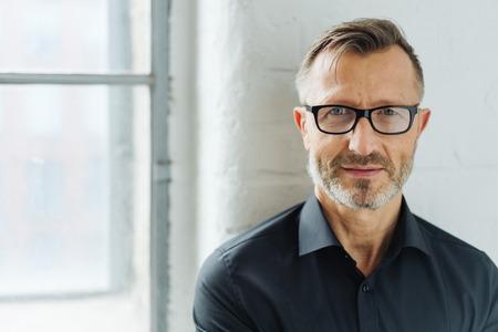 Tragende Gläser des bärtigen Mannes von mittlerem Alter, die Kamera mit einem ernsten Ausdruck in einem Abschluss herauf Haupt- und Schulterporträt betrachten