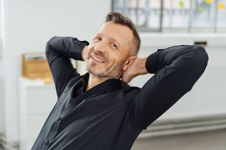 Confident relaxed businessman smiling at the camera as he leans back in his chair with his hands behind his head