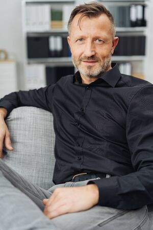 Thoughtful middle-aged man looking at the camera with a quiet smile as he relaxes on a sofa at home