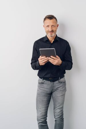 Relaxed mature man in jeans standing holding a tablet while looking at the camera with a smile over a white interior wall Banque d'images
