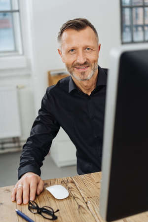 Friendly businessman looking around a large desktop monitor at the camera with a smile