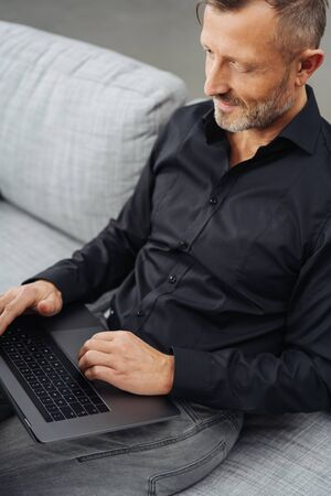 Businessman working on his laptop at home as he relaxes on a sofa in a close up high angle cropped view