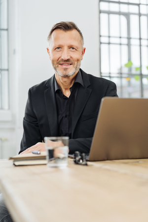 Businessman sitting at an office table with a laptop smiling at the camera in a low angle view with foreground copy space