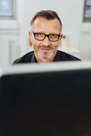 Businessman wearing glasses smiling at the camera over the top of a large desktop monitor Banque d'images