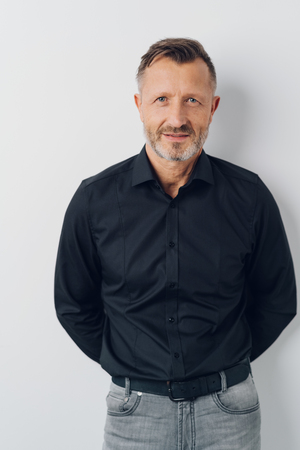 Serious attractive casual middle-aged man posing with his hands behind his back over an interior white wall looking at the camera Stock Photo