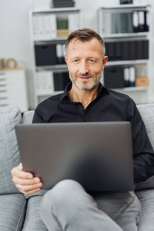 Smiling man sitting at home on a couch browsing on a laptop computer balanced on his lap