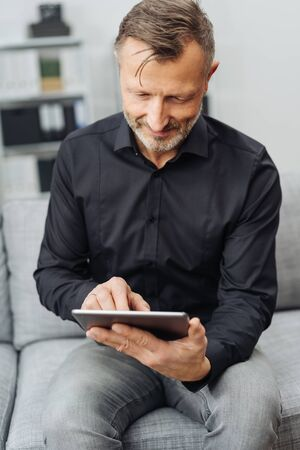 Smiling middle-aged man sitting using a handheld tablet-pc at home on a sofa in a close up view Banque d'images