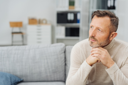 Thoughtful middle-aged man with a faraway expression sitting on a sofa at home looking off to the side with copy space