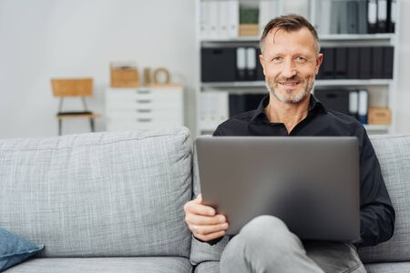 Attractive middle-aged man relaxing with a laptop at home on a sofa in his living room sitting smiling at the camera Banque d'images