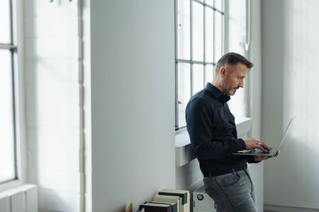 Man sitting perched on a radiator using a laptop computer in front of a bright window in an airy white room with copy space
