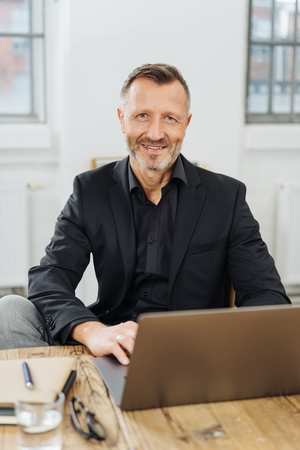 Confident manager working on a laptop computer in a bright office looking at the camera with a friendly pleased smile Stock Photo