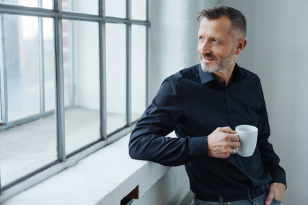 Businessman taking a coffee break standing leaning against a windowsill turning to stare out with a thoughtful expression