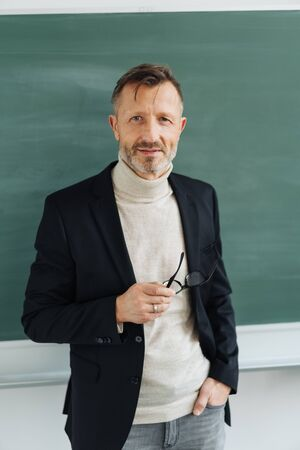 Attractive elegant professor or teacher standing in a classroom in front of a blank chalkboard holding his glasses in his hand smiling at the camera