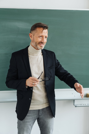 Male teacher taking a question from the class as he stands in front of a blank chalk board extending his hand Banque d'images