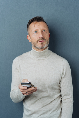 Thoughtful man holding a mobile phone standing against a dark studio background staring up with a pensive expression