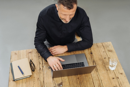 High-angle view of a middle-aged man using a laptop during work at his desk in a modern business office