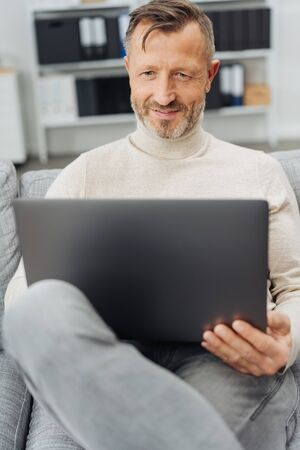 Man sitting relaxing at home with his laptop on a comfortable sofa smiling as he browses the internet