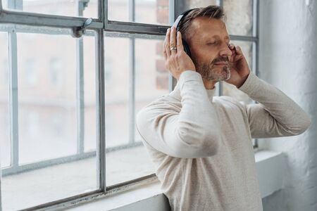 Attractive middle-aged man listening to music on stereo headphones as he leans back against a bright window