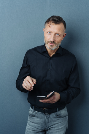 Serious thoughtful businessman holding a smartphone looking up at the camera with an attentive look against a dark grey studio background