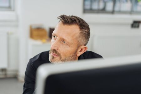 Thoughtful businessman watching to the side with a serious expression viewed over a large desktop monitor Banque d'images
