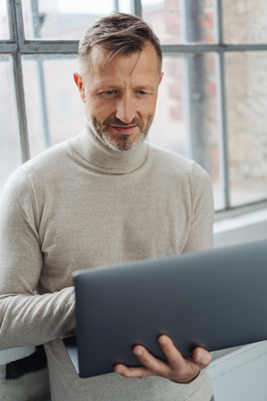 Middle-aged man working on a handheld laptop computer as he stands in front of a large window in a close up view Banque d'images
