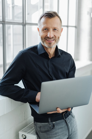 Friendly smiling businessman holding an open laptop as he perches on a radiator in front of a large window Banque d'images
