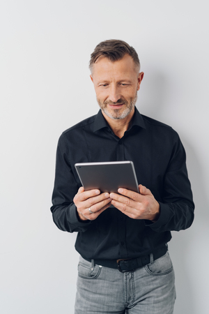 Studio shot portrait of a middle-aged handsome man smiling while reading online information on a tablet PC against gray background for copy space
