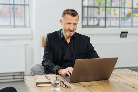 Businessman sitting working at a laptop computer in a large office typing information with a look of concentration