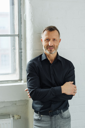Attractive bearded middle-aged man with folded arms standing indoors alongside a window staring at the camera Stock Photo
