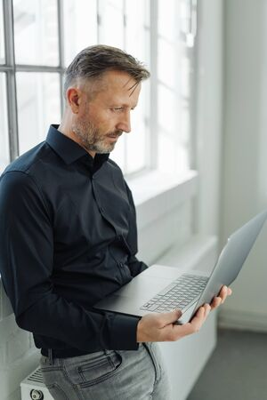 Businessman using a handheld laptop computer as he sits perched on a large radiator below a bright window