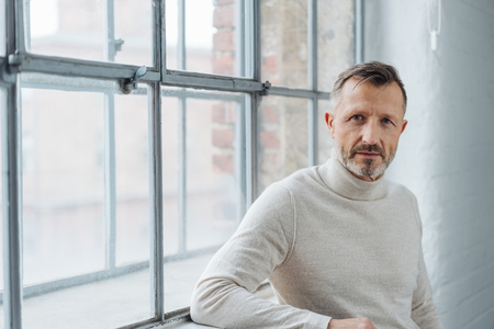 Serious stylish middle-aged man staring at the camera with a penetrating look as he leans against the sill of a large window Stock Photo