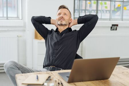 Successful businessman sitting pondering a problem or new idea relaxing back in his chair at the office with his hands behind his head Banque d'images